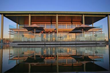 large modern glass and copper building winery water pool in front